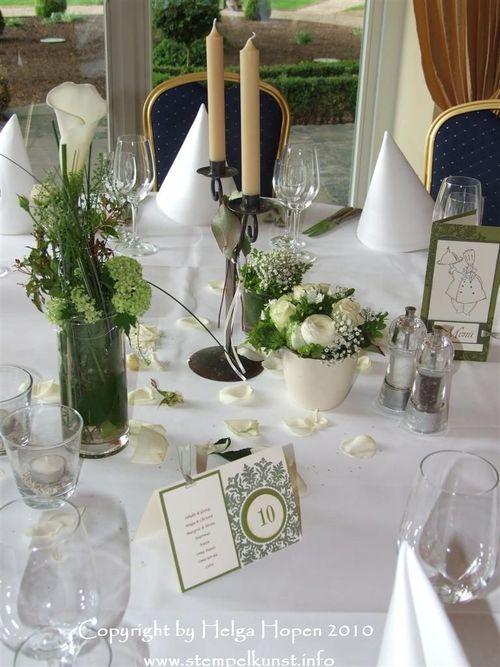 Hier ein Foto von einem Tisch mit Blumenschmuck, den Tisch- und ...